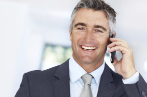 Confident mature executive having an amiable conversation on his cellphone - Copyspace